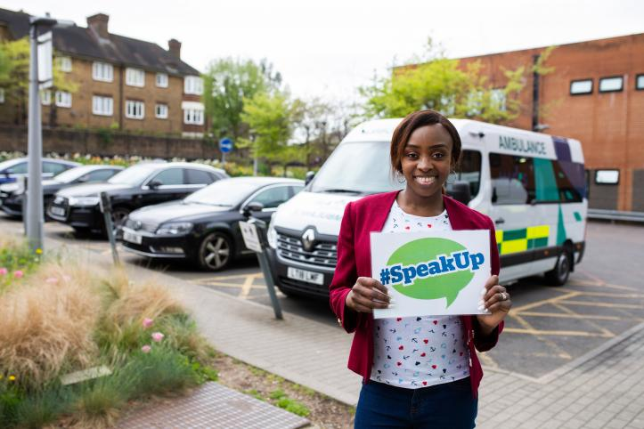 lady holding Speak Out Card