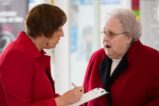 A receptionist showing a lady how to fill in a form