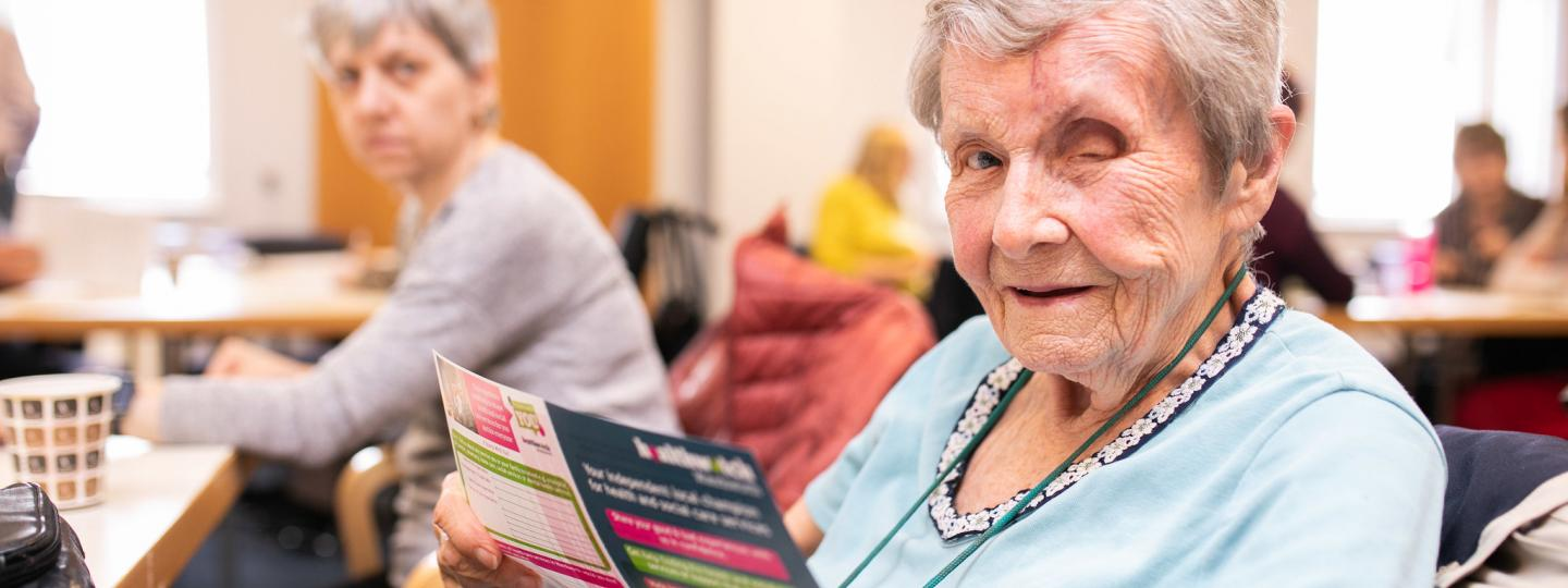 An old lady with one eye, holding a healthwatch leaflet