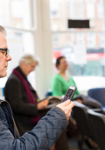 Man in waiting room looking at a mobile phone
